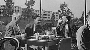 Three men chatting at a table, with trees, lawns, and apartments in the background